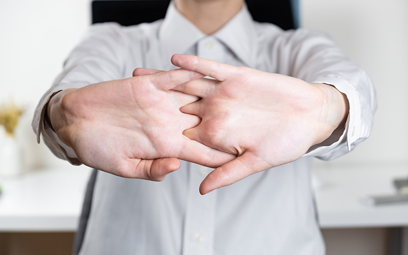 Stretching arms in sparse office workplace. Hands of an employee in front of modern desktop, accomplished work concept