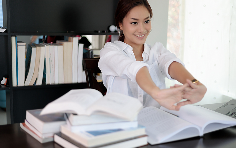 Asian woman stretching after reading book and work hard and smiling in the home office