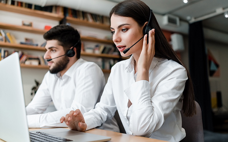 beautiful woman works in call center with headset answering client phone calls
