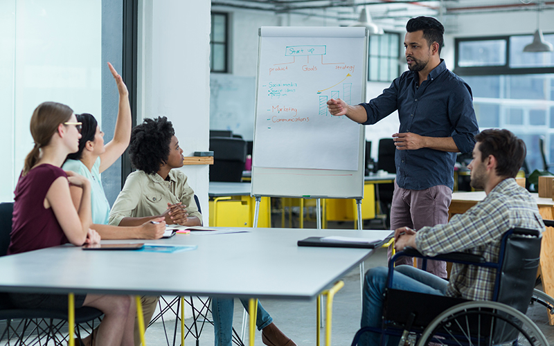 Business executives discussing over flip chart during meeting in office